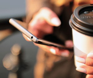 Lady holding smartphone with a cup of coffee.