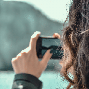 A lady holding her smartphone horizontally to capture the mountain in the background.