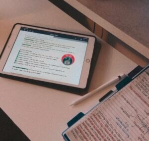 An iPad displaying hand written notes next to a notepad.